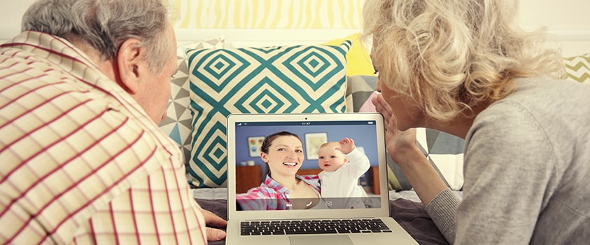 Grandparents video chatting with daughter and granddaughter