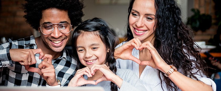 Family making hearts with their hands while looking at a laptop screen and webcam
