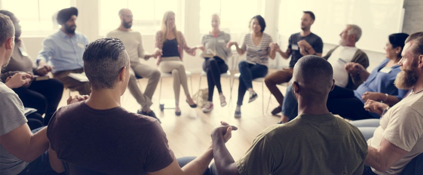 Support Group - people sitting in a circle holding hands